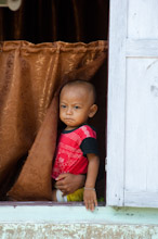 HAL110610A0017  Local child looking out of window, Halmahera, Maluku Islands, Indonesia